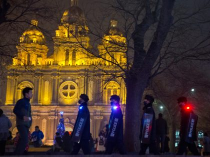 Police officers with shields march past the Dongtang Catholic church in Beijing, China, Thursday, Dec. 24, 2015. Beijing police announced Thursday that they had issued a yellow security alert to ensure safety during the Christmas period. (AP Photo/Ng Han Guan)