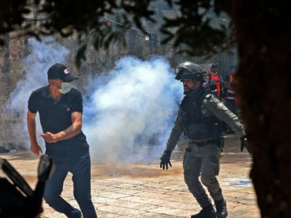 Palestinians run for cover from tear gas fired by Israeli security forces in Jerusalem's Old City on May 10, 2021, ahead of a planned march to commemorate Israel's takeover of Jerusalem in the 1967 Six-Day War. (Photo by EMMANUEL DUNAND / AFP) (Photo by EMMANUEL DUNAND/AFP via Getty Images)