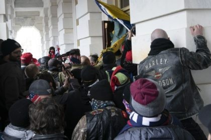 In this Jan. 6, 2021 file photo insurrectionists loyal to President Donald Trump try to open a door of the U.S. Capitol as they riot in Washington. With riot cases flooding into Washington's federal court, the Justice Department is under pressure to quickly resolve the least serious cases. (AP Photo/Jose …