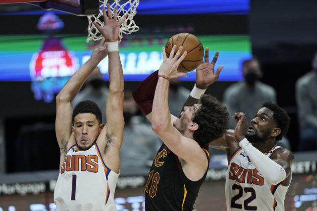 Phoenix Suns' Devin Booker (1) and Deandre Ayton (22) defend against Cleveland Cavaliers' Cedi Osman (16) in the second half of an NBA basketball game, Tuesday, May 4, 2021, in Cleveland. Phoenix won 134-118 in overtime. (AP Photo/Tony Dejak)