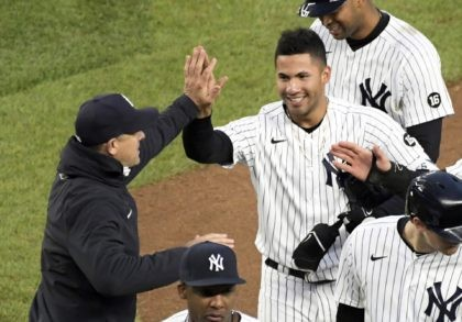 New York Yankees' Gleyber Torres is congratulated by manager Aaron Boone after Torres drove in the winning run in the 11th inning of the team's baseball game against the Washington Nationals on Saturday, May 8, 2021, at Yankee Stadium in New York. The Yankees won 4-3. (AP Photo/Bill Kostroun)