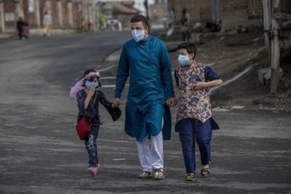 A Kashmiri man along with his children walks on a deserted road, as Kashmiris marked Eid during lockdown to curb the spread of coronavirus in Srinagar, Indian controlled Kashmir, Thursday, May 13, 2021. (AP Photo/ Dar Yasin)