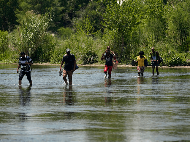 A group of migrants walk across the Rio Grande on their way to turn themselves in upon crossing the U.S.-Mexico border, Tuesday, June 15, 2021, in Del Rio, Texas. U.S. government data shows that 42% of all families encountered along the border in May hailed from places other than Mexico, …