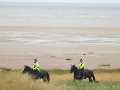 Police on horseback walk along the beach on the periphery of the Royal Liverpool golf club, Hoylake, England on Wednesday July 16, 2014, where the British Open Golf championship will take place Thursday July 17. (AP Photo/Peter Morrison)