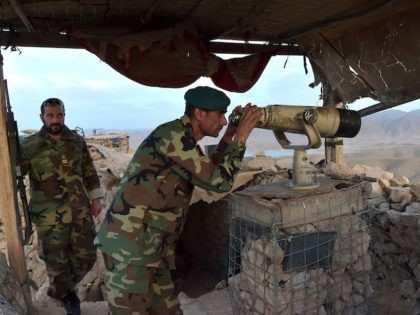 In this photograph taken on March 23, 2021, Afghan National Army (ANA) commander Dost Nazar Andarabi keeps watch with binoculars at an outpost set up against Taliban fighters in Kajaki, northeast of Helmand Province. - In the heart of territory under siege from the Taliban, one of Afghanistan's most important …