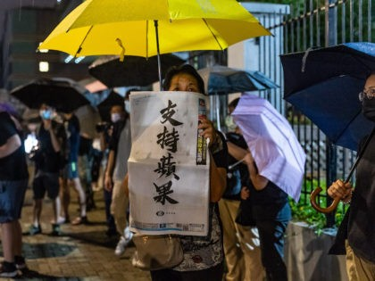 A supporter holds up a copy of the Apple Daily newspaper outside of their offices on June 23, 2021 in Hong Kong, China. Hong Kong's largest pro-democracy newspaper announced it would be printing its final issue on Thursday after its offices were raided last week over allegations that reports had …