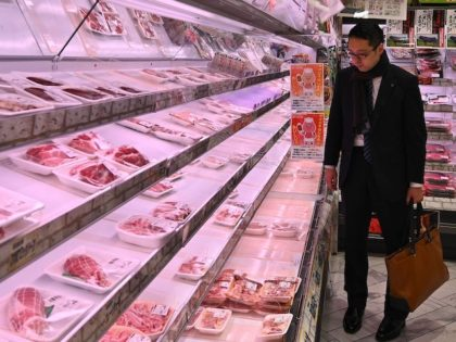 A man looks at meat on nearly empty shelves in a supermarket in Tokyo on March 27, 2020. (Photo by Philip FONG / AFP) (Photo by PHILIP FONG/AFP via Getty Images)