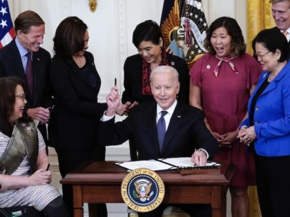 President Joe Biden hands out a pen after signing the COVID-19 Hate Crimes Act, in the East Room of the White House, Thursday, May 20, 2021, in Washington. Clockwise from left, Sen. Tammy Duckworth, R-Ill., Sen. Richard Blumenthal, D-Conn., Vice President Kamala Harris, Rep. Judy Chu, D-Calif., Rep. Grace Meng, …