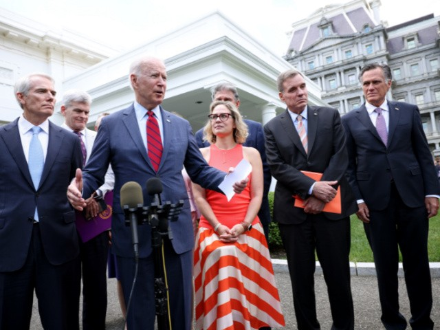 President Joe Biden speaks outside the White House with a bipartisan group of senators after a meeting about an infrastructure deal June 24, 2021, in Washington, DC. From left to right are Sen. Rob Portman (R-OH), Sen. Bill Cassidy (R-LA), Sen. Kyrsten Sinema (D-AZ), Sen. Joe Manchin (D-WV), Sen. Mark Warner (D-VA), and Sen. Mitt Romney (R-UT). (Kevin Dietsch/Getty Images)