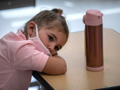 STAMFORD, CONNECTICUT - SEPTEMBER 09: Harper Shea (5), lays her head down on her desk near the end of her first day of kindergarten on September 9, 2020 in Stamford, Connecticut. For millions of kindergartners attending in-school classes for the first time, wearing masks and social distancing at school isn't …