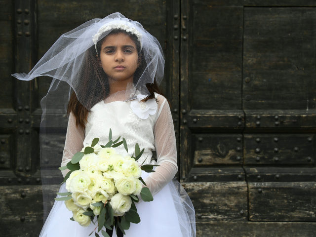 A young actress plays the role of Giorgia, 10, forced to marry Paolo, 47, during a happening organised by Amnesty International to denounce child marriage, on October 27, 2016 in Rome. (Photo by GABRIEL BOUYS / AFP) (Photo by GABRIEL BOUYS/AFP via Getty Images)