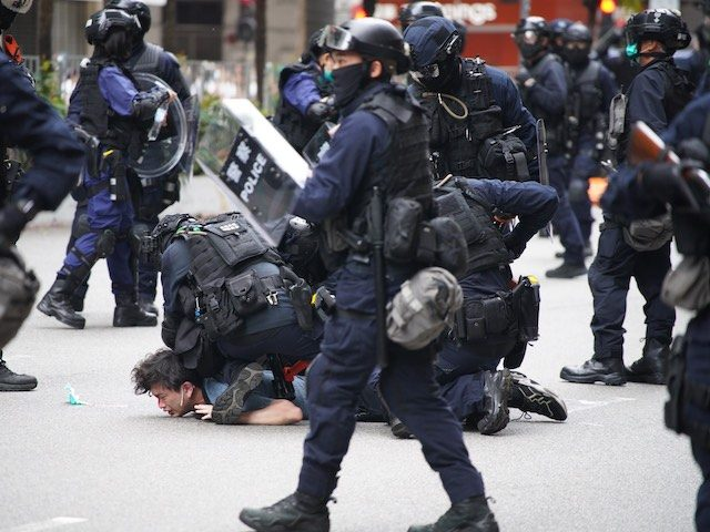 Police special tactical squad detain a protester (C) in Wanchai, Hong Kong on May 24, 2020, as thousands of demonstrators took to the streets to protest against a national security law. - The proposed legislation is expected to ban treason, subversion and sedition, and follows repeated warnings from Beijing that …