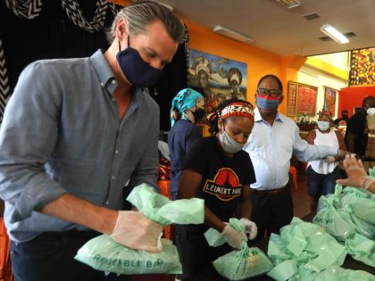 California Governor Gavin Newsom (L) helps pack up lunches to be delivered to needy senior citizens, along with Hot and Cool Cafe co-owner Shana Jenson (2nd L), Los Angeles Supervisor Mark Ridley-Thomas and California Assembly Member Sydney Kamlager-Dove (R) during a visit to the cafe in Leimert Park in Los …