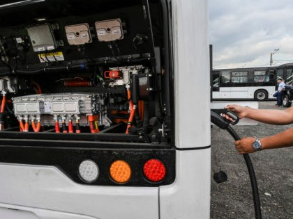 A man charges a new imported electric bus in Medellin, Colombia, on September 17, 2019. - A new fleet of 64 electric buses is the second largest in a Latin America city and will start operating in November, according to local authorities. (Photo by JOAQUIN SARMIENTO / AFP) (Photo credit …