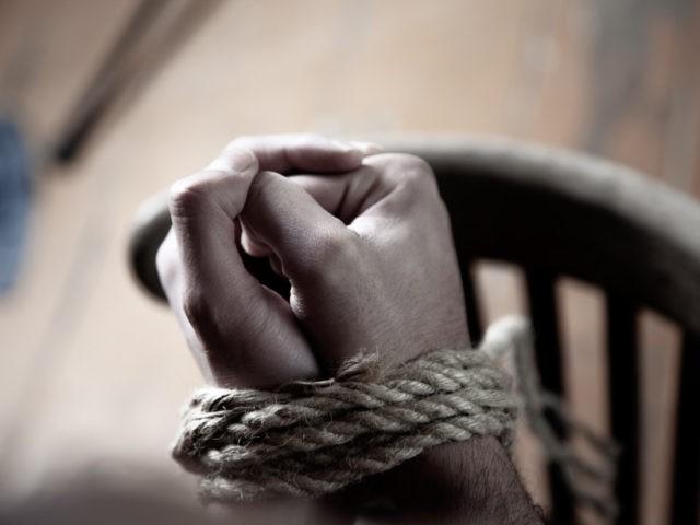 man hands tied on dark background