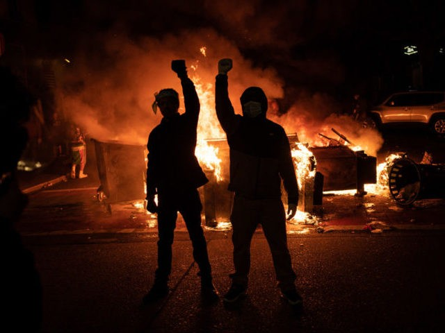 SEATTLE, WA - JUNE 08: Demonstrators raise their fists as a fire burns in the street after clashes with law enforcement near the Seattle Police Departments East Precinct shortly after midnight on June 8, 2020 in Seattle, Washington. Earlier in the evening, a suspect drove into the crowd of protesters …