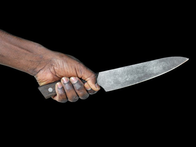 African man hold knife - aggression. Big kitchen knife in man hand. Large kitchen knife in a man's hand. Hand of african man holding a knife isolated on a black background.