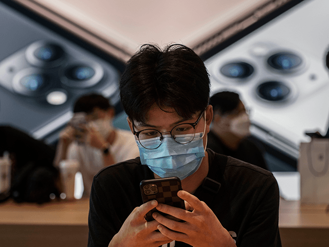 A Chinese customer looks at a phone at the official opening of the new Apple Store in the Sanlitun shopping area on July 17, 2020 in Beijing, China. The new store replaces Apple's first ever China store which opened in 2008 prior to the Beijing Olympics adjacent to the new …