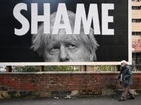 A man wearing a protective face mask passes a billboard showing Britain's Prime Minister Boris Johnson in Manchester, north-west England on November 6, 2020, as the second lockdown comes into force in England. - A united effort to tackle spiking coronavirus infection rates has been called for as 56 million …