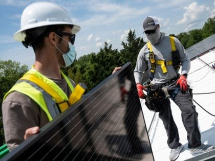 Employees with Ipsun Solar unload solar panels on the roof of the Peace Lutheran Church in Alexandria, Virginia on May 17, 2021. - Using donations, the church installed a 60.48 kilowatt solar instillation to bring down their carbon footprint. US President Joe Biden has called for the US energy sector …