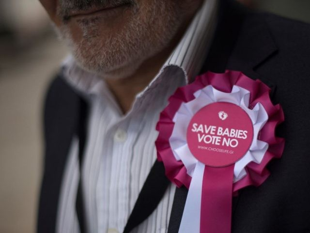 A man wears a rosette against abortion outside a polling station in Gibraltar, on June 24, 2021, during a referendum to ease an abortion law. - Gibraltar began voting on plans to ease its draconian abortion law in a referendum delayed for over a year by the coronavirus pandemic. The …