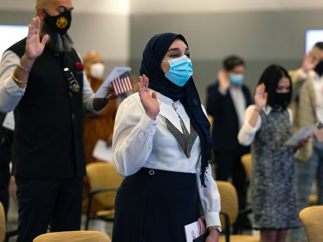 CAMP SPRINGS, MARYLAND - MAY 27: New U.S. Citizens take their Oath of Allegiance during a naturalization ceremony at the United States Citizenship and Immigration Services (USCIS) Headquarters on May 27, 2021 in Camp Springs, Maryland. This special Naturalization Ceremony honored Asian American Pacific Islanders and was the first ceremony …