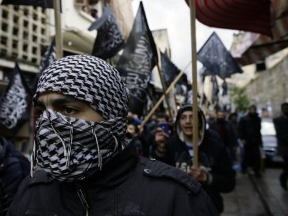 Lebanese supporters of the Sunni Islamist party Al-Tahrir wave the party's flags as they march in the streets of the northern city of Tripoli after the Friday prayers during a demonstration against the Syrian regime on January 27, 2012. AFP PHOTO/JOSEPH EID (Photo credit should read JOSEPH EID/AFP via Getty …