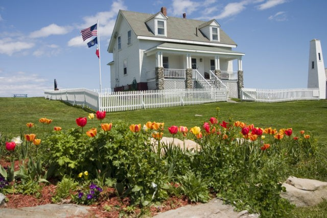 View of lighthouse keepers cottage with tulip bed in foreground.