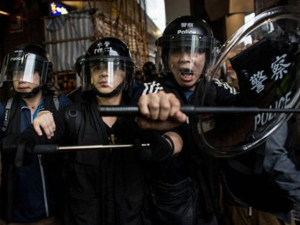 HONG KONG - DECEMBER 01: Police advance on pro-democracy protesters at the Admiralty MTR station on December 1, 2014 in Hong Kong. Leaders from the Federation of Students called on fellow protesters to attend a rally and come prepared for escalated action. Protesters were asked to bring masks, umbrellas and …
