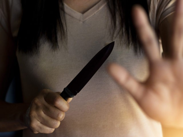 Woman holding a knife in hand while defending herself from attacks.