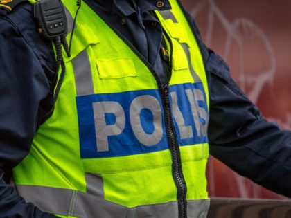 Close up of Swedish police officer wearing a luminous yellow green vest with police text. Only upper body visible, no recognizable person.