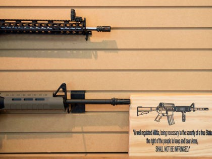 A placard about gun rights in the United States hangs on the wall next to assault rifles for sale at Blue Ridge Arsenal in Chantilly, Virginia, on October 6, 2017. (Photo by JIM WATSON / AFP) (Photo credit should read JIM WATSON/AFP via Getty Images)