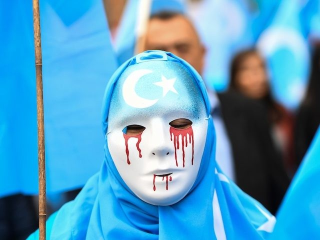 """TOPSHOT - A person wearing a white mask with tears of blood takes part in a protest march of ethnic Uighurs asking for the European Union to call upon China to respect human rights in the Chinese Xinjiang region and ask for the closure of """"re-education center"""" where Uighurs are …"""