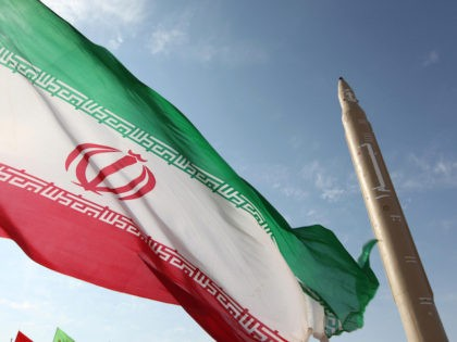 A picture taken on August 20, 2010 shows an Iranian flag fluttering at an undisclosed location in the Islamic republic next to a surface-to-surface Qiam-1 (Rising) missile which was test fired a day before Iran was due to launch its Russian-built first nuclear power plant. Iranian Defence Minister Ahmad Vahidi …