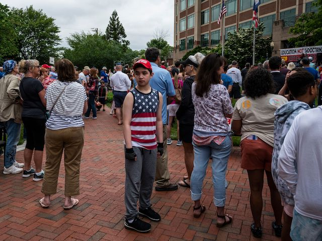 """A young boy walks through the crowd during a rally against """"critical race theory"""" (CRT) being taught in schools at the Loudoun County Government center in Leesburg, Virginia on June 12, 2021. - """"Are you ready to take back our schools?"""" Republican activist Patti Menders shouted at a rally opposing anti-racism teaching that critics like her say trains white children to see themselves as """"oppressors."""" """"Yes!"""", answered in unison the hundreds of demonstrators gathered this weekend near Washington to fight against """"critical race theory,"""" the latest battleground of America's ongoing culture wars. The term """"critical race theory"""" defines a strand of thought that appeared in American law schools in the late 1970s and which looks at racism as a system, enabled by laws and institutions, rather than at the level of individual prejudices. But critics use it as a catch-all phrase that attacks teachers' efforts to confront dark episodes in American history, including slavery and segregation, as well as to tackle racist stereotypes. (Photo by ANDREW CABALLERO-REYNOLDS / AFP) (Photo by ANDREW CABALLERO-REYNOLDS/AFP via Getty Images)"""