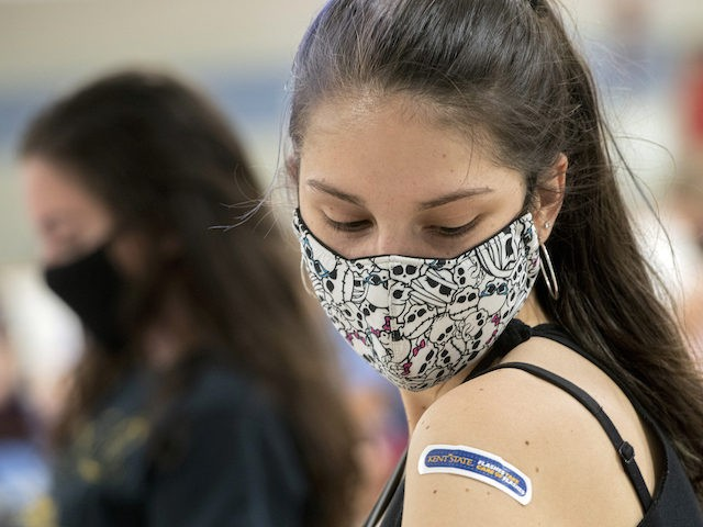 Kent State University student Regan Raeth of Hudson, Ohio, looks at her vaccination bandage as she waits for 15 minutes after her shot in Kent, Ohio, Thursday, April 8, 2021. (AP Photo/Phil Long)