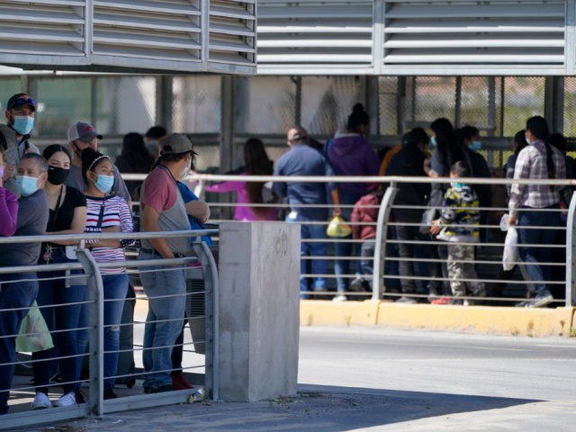 Travelers, left, waiting in line to cross a customs area into the United States at the McAllen-Hidalgo International Bridge look on as a group of migrants, right, are deported to Reynosa, Mexico, Thursday, March 18, 2021, in Hidalgo, Texas. A surge of migrants on the Southwest border has the Biden …