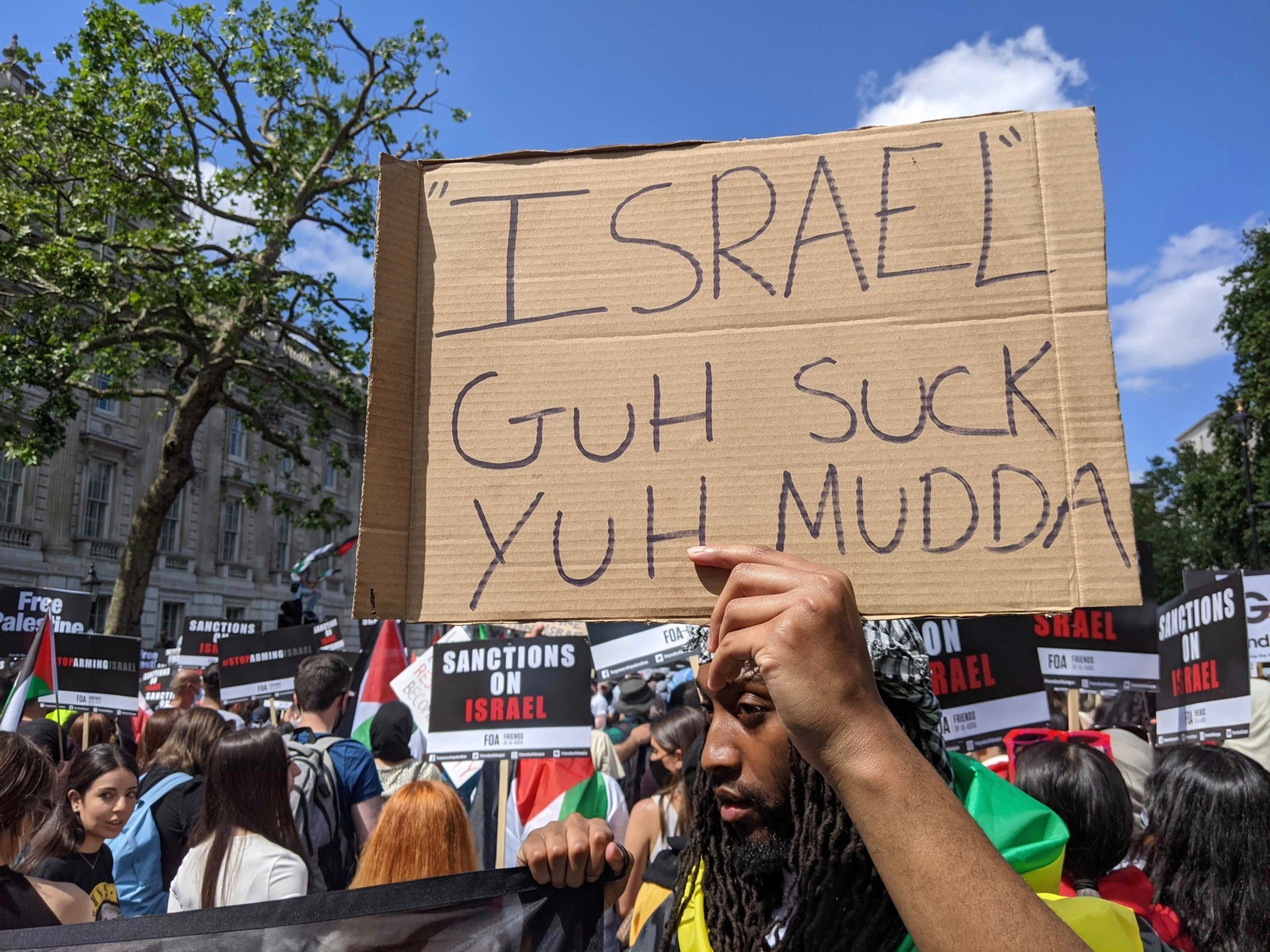 """A pro-Palestine protester holds a placard reading """"Israel Guh Suck Yuh Mudda"""" at a Downing Street protest. June 12th, 2021. Kurt Zindulka, Breitbart News"""