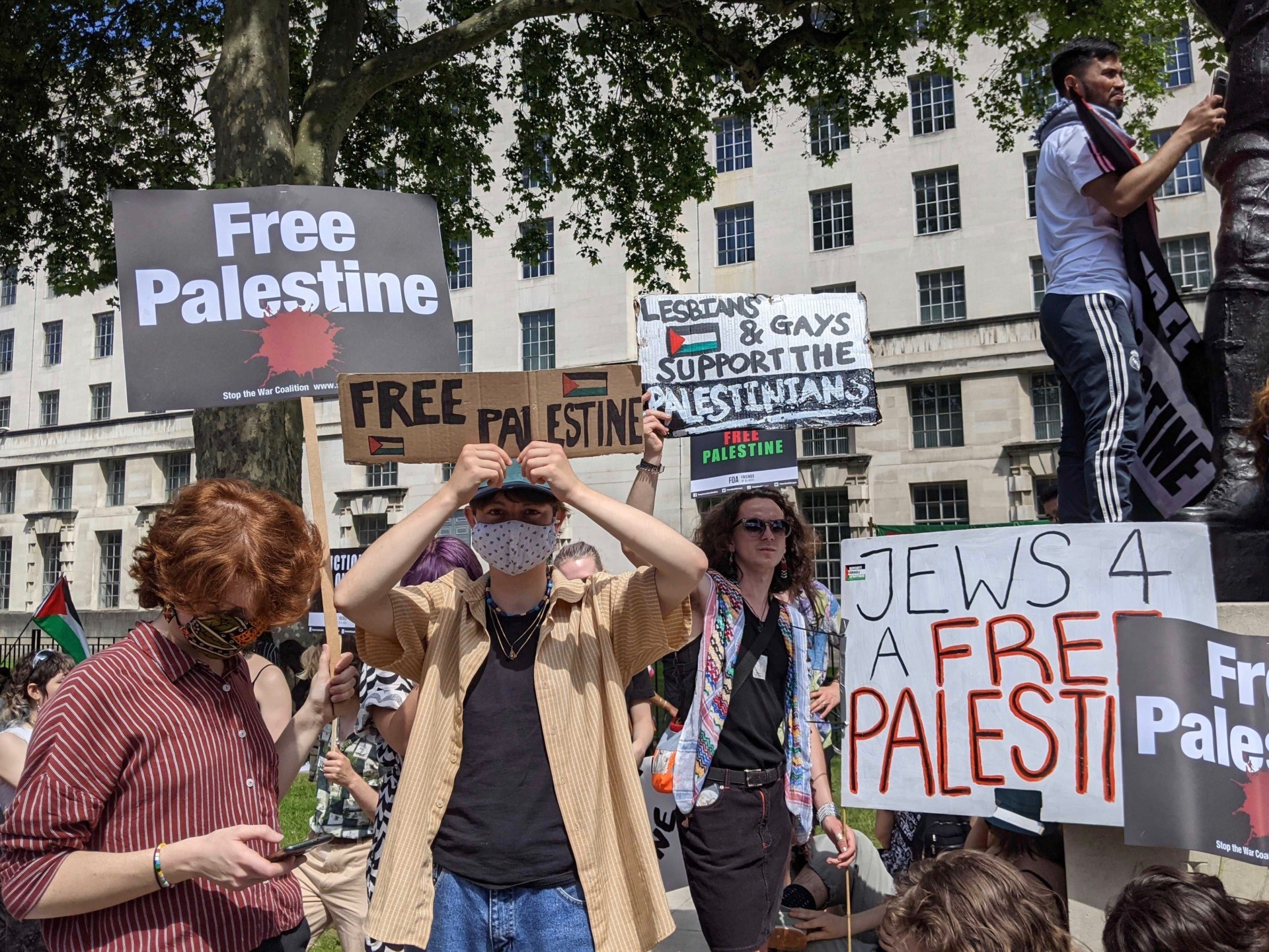 """Anti-Isreal protester holds a placard reading """"Lesbians and Gays Support the Palestinians"""" at a Downing Street protest. June 12th, 2021. Kurt Zindulka, Breitbart News"""