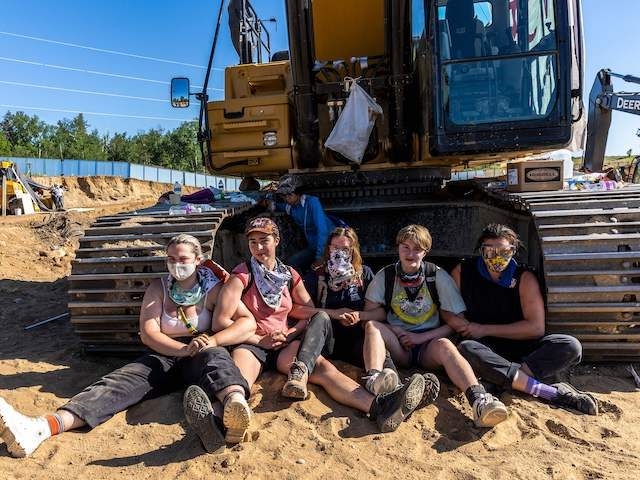 Environmental activists chain themselves to construction equipment at the Line 3 pipeline pumping station near the Itasca State Park, Minnesota on June 7, 2021. - Line 3 is an oil sands pipeline which runs from Hardisty, Alberta, Canada to Superior, Wisconsin in the United States. In 2014, a new route …