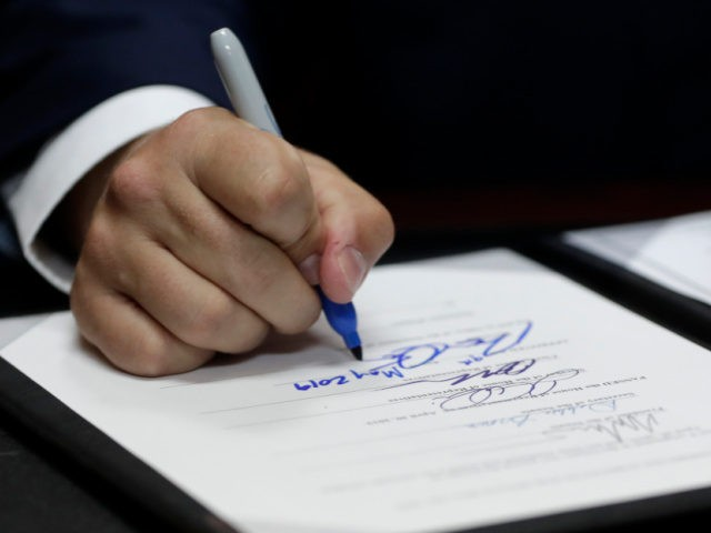 Florida Gov. Ron DeSantis signs a bill during a signing ceremony at the William J. Kirlew Junior Academy, Thursday, May 9, 2019, in Miami Gardens, Fla. The bill creates a new voucher program for thousands of students to attend private and religious schools using taxpayer dollars traditionally spent on public …