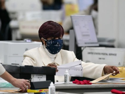 Absentee ballots are processed at the central counting board, Wednesday, Nov. 4, 2020, in Detroit. (AP Photo/Carlos Osorio)