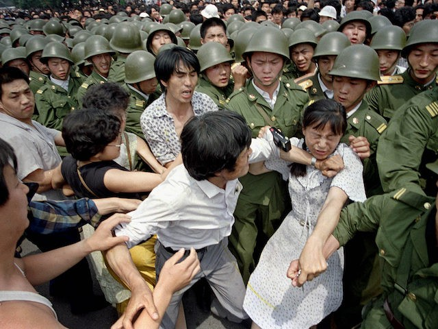 A young woman is caught between civilians and Chinese soldiers, who were trying to remove her from an assembly near the Great Hall of the People in Beijing, June 3, 1989. Pro-democracy protesters had been occupying Tiananmen Square for weeks. (AP Photo/Jeff Widener)