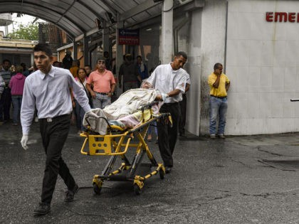 A patient of the University Hospital is transported in a stretcher outside the building in Barquisimeto, Venezuela on April 24, 2019. - Venezuela is facing the worst crisis in its modern history with inflation expecting to soar a mind-boggling 10 million percent this year, contributing to a shortage of basic …
