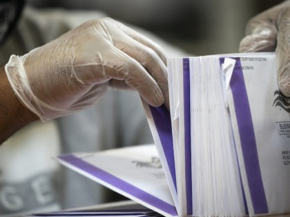 A canvasser wears gloves while processing mail-in ballots in a warehouse at the Anne Arundel County Board of Elections headquarters on October 7, 2020 in Glen Burnie, Maryland. The ballot canvas for mail-in and absentee ballots began on October 1st in Maryland, the earliest in the country. Every ballot goes …