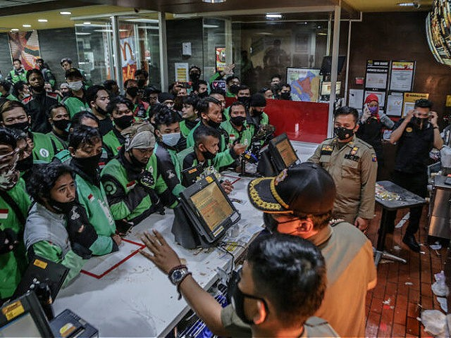 Food delivery riders queue up at a McDonalds outlet in Bogor on June 9, 2021, to buy the new BTS-meal deal for hungry fans in the K-Pop mad country, causing more than a dozen McDonald's outlets to temporarily shuttered over virus fears. (Photo by ADITYA AJI / AFP) (Photo by …