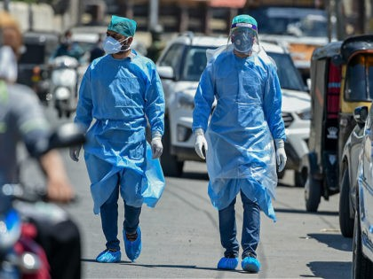 Doctors wearing protective gear walk among vehicles during a government-imposed nationwide lockdown as a preventive measure against the COVID-19 coronavirus, on the outskirts of Srinagar on May 8, 2020. (Photo by Tauseef MUSTAFA / AFP) (Photo by TAUSEEF MUSTAFA/AFP via Getty Images)
