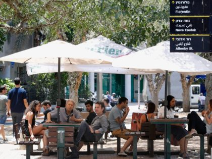 Israelis sit at a coffee shop in Tel Aviv on May 27, 2020 as restaurants were allowed to open for the first time in months after the Israeli government approved the easing of measures put in place to stop the spread of the coronavirus Covid-19. (Photo by JACK GUEZ / …