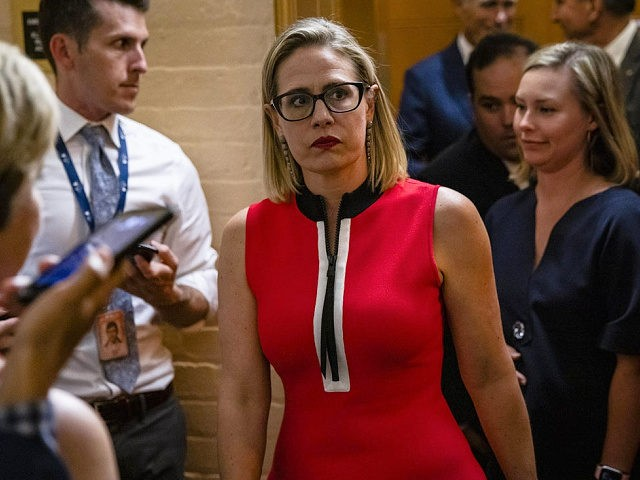 WASHINGTON, DC - JUNE 08: U.S. Sen. Kirsten Sinema (D-AZ) heads back to a bipartisan meeting on infrastructure in the basement of the U.S. Capitol building after the original talks fell through with the White House on June 8, 2021 in Washington, DC. Senate Majority Leader Chuck Schumer (D-NY) said …