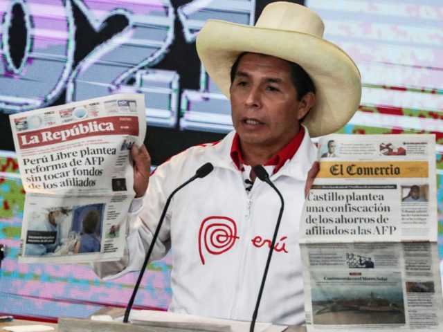 Peruvian presidential candidate, socialist Pedro Castillo, shows newspaper headlines during the last debate with his opponent, right-wing candidate Keiko Fujimori, ahead of the June 6 run-off election, in Arequipa, Peru, on May 30, 2021. (Photo by SEBASTIAN CASTANEDA / X07403 / AFP) (Photo by SEBASTIAN CASTANEDA/X07403/AFP via Getty Images)